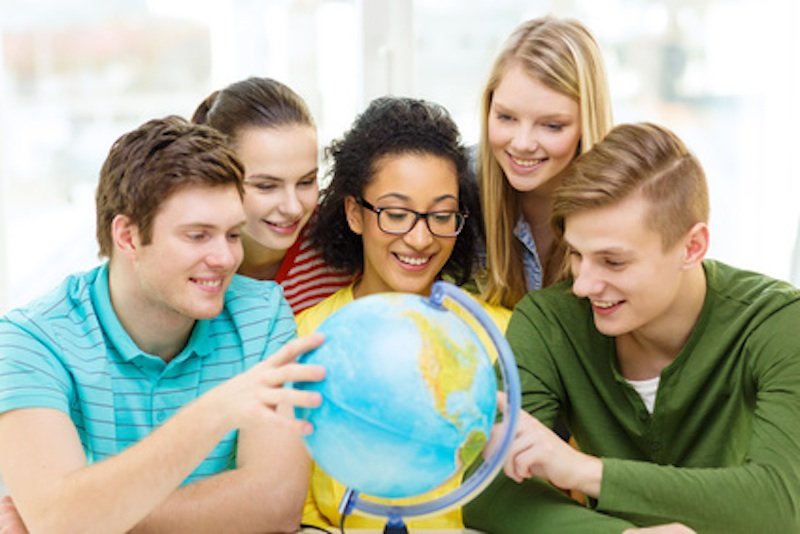 five smiling student looking at globe at school